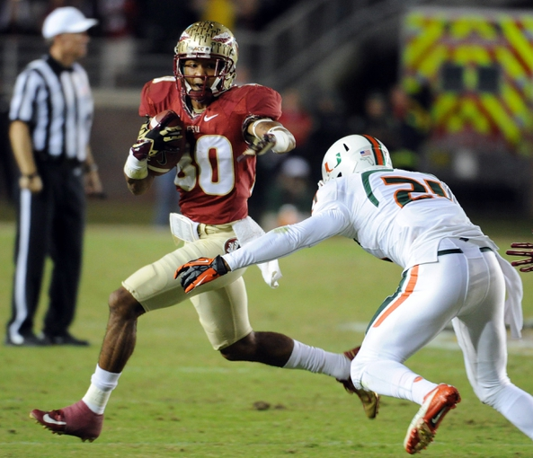 Nov 2, 2013; Tallahassee, FL, USA; Florida State Seminoles wide receiver Rashad Greene (80) runs the ball past Miami Hurricanes defensive back Ray Lewis III (20) during the second half at Doak Campbell Stadium. Mandatory Credit: Melina Vastola-USA TODAY Sports