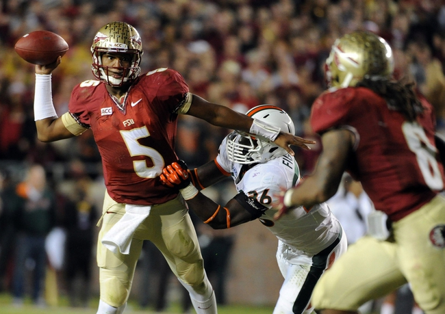 Nov 2, 2013; Tallahassee, FL, USA; Florida State Seminoles quarterback Jameis Winston (5) evades Miami Hurricanes linebacker Alex Figueroa (36) as he throws the ball during the second half at Doak Campbell Stadium. Mandatory Credit: Melina Vastola-USA TODAY Sports