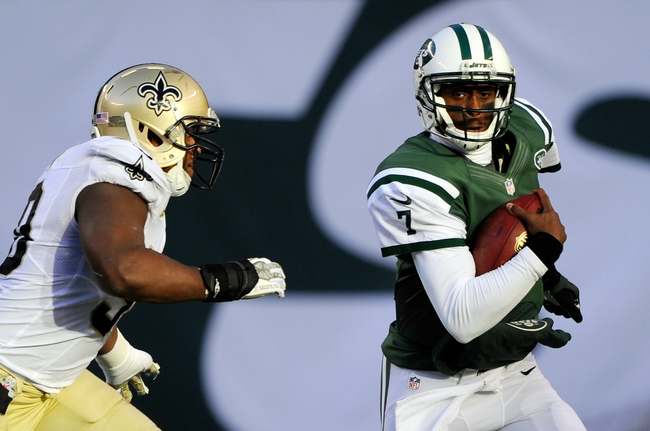 Nov 3, 2013; East Rutherford, NJ, USA; New York Jets quarterback Geno Smith (7) scrambles away from New Orleans Saints middle linebacker Curtis Lofton (50) in the second half during the game at MetLife Stadium. Mandatory Credit: Robert Deutsch-USA TODAY Sports