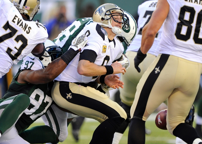 Nov 3, 2013; East Rutherford, NJ, USA; New Orleans Saints quarterback Drew Brees (9) fumbles the ball as he is sacked by New York Jets outside linebacker Calvin Pace (97) during the game at MetLife Stadium. Mandatory Credit: Robert Deutsch-USA TODAY Sports
