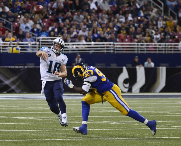 Nov 3, 2013; St. Louis, MO, USA; Tennessee Titans quarterback Jake Locker (10) attempts a pass as St. Louis Rams defensive end William Hayes (95) pressures during the second half at the Edward Jones Dome. The Titans defeated the Rams 28-21. Mandatory Credit: Scott Rovak-USA TODAY Sports