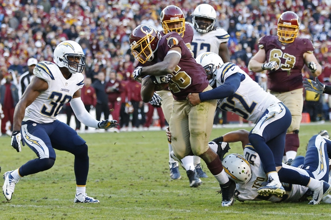 Nov 3, 2013; Landover, MD, USA; Washington Redskins running back Alfred Morris (46) runs with the ball as San Diego Chargers free safety Eric Weddle (32) defends in overtime at FedEx Field. The Washington Redskins won 30-24 in overtime. Mandatory Credit: Geoff Burke-USA TODAY Sports