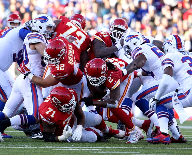 Nov 3, 2013; Orchard Park, NY, USA; Kansas City Chiefs running back Jamaal Charles (25) dives through the pile during the second half against the Buffalo Bills at Ralph Wilson Stadium. Chiefs beat the Bills 23 to 13.  Mandatory Credit: Timothy T. Ludwig-USA TODAY Sports