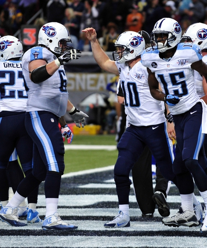 Nov 3, 2013; St. Louis, MO, USA; Tennessee Titans quarterback Jake Locker (10) is congratulated by teammates after scoring a touchdown against the St. Louis Rams during the second half at the Edward Jones Dome. The Titans defeated the Rams 28-21. Mandatory Credit: Scott Rovak-USA TODAY Sports