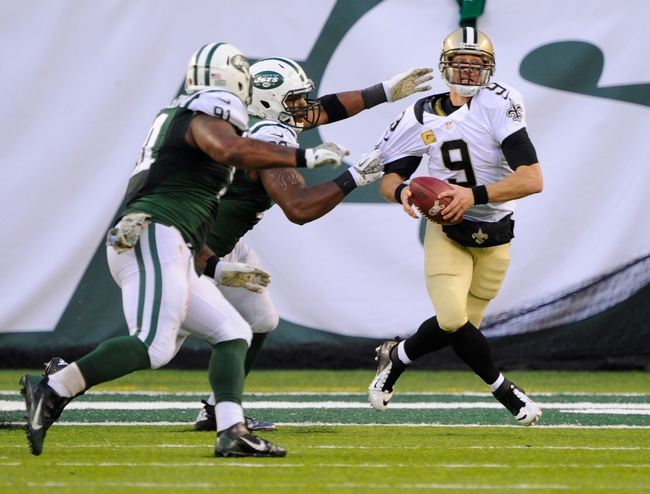 Nov 3, 2013; East Rutherford, NJ, USA; New Orleans Saints quarterback Drew Brees (9) is pressured by New York Jets outside linebacker Quinton Coples during the game at MetLife Stadium. Mandatory Credit: Robert Deutsch-USA TODAY Sports
