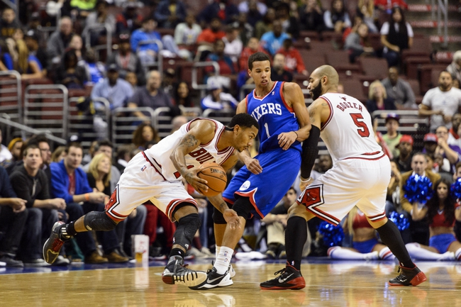 Nov 2, 2013; Philadelphia, PA, USA; Chicago Bulls guard Derrick Rose (1) is defended by Philadelphia 76ers guard Michael Carter-Williams (1) as forward Carlos Boozer (5) sets a pick during the fourth quarter at Wells Fargo Center. The Sixers defeated the Bulls 107-104. Mandatory Credit: Howard Smith-USA TODAY Sports