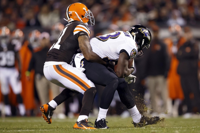 Nov 3, 2013; Cleveland, OH, USA; Cleveland Browns cornerback Chris Owens (21) attempts to bring down Baltimore Ravens wide receiver Deonte Thompson (83) in the fourth quarter at FirstEnergy Stadium. Mandatory Credit: Rick Osentoski-USA TODAY Sports