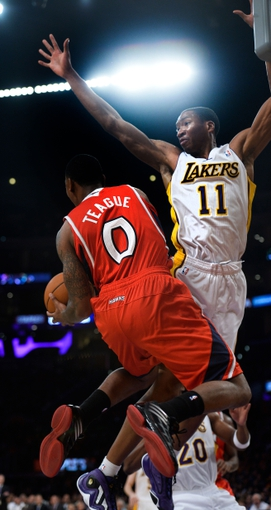 Nov 3, 2013; Los Angeles, CA, USA; Atlanta Hawks point guard Jeff Teague (0) hangs in the air as he passes off to a teammate as Los Angeles Lakers shooting guard Wesley Johnson (11) tries to defend during second quarter action at Staples Center. Mandatory Credit: Robert Hanashiro-USA TODAY Sports