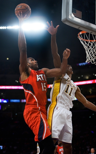 Nov 3, 2013; Los Angeles, CA, USA; Atlanta Hawks center Al Horford (15) puts up a shot past the outstretched arm of Los Angeles Lakers shooting guard Wesley Johnson (11) during second quarter action at Staples Center. Mandatory Credit: Robert Hanashiro-USA TODAY Sports