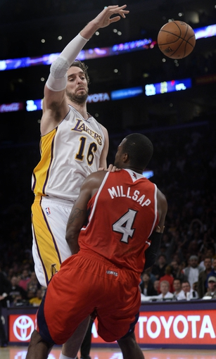 Nov 3, 2013; Los Angeles, CA, USA; Atlanta Hawks power forward Paul Millsap (4) is called for a blocking foul on as Los Angeles Lakers power forward Pau Gasol (16) drives to the hoop and passes off in the closing seconds at Staples Center. The score was tied at the time, Gasol made both free throws.  Mandatory Credit: Robert Hanashiro-USA TODAY Sports