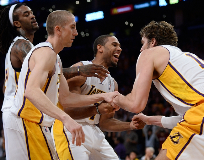 Nov 3, 2013; Los Angeles, CA, USA; Los Angeles Lakers shooting guard Xavier Henry (7) smiles as he helps up teammate Paul Gasol (16, right) after Gasol was fouled by the Atlanta Hawks Paul Milsap (not pictured) in the closing seconds at Staples Center. Gasol made two free throws and the Lakers went on to a 105-103 win. Left is the Lakers Steve Blake and Jordan Hill. Mandatory Credit: Robert Hanashiro-USA TODAY Sports