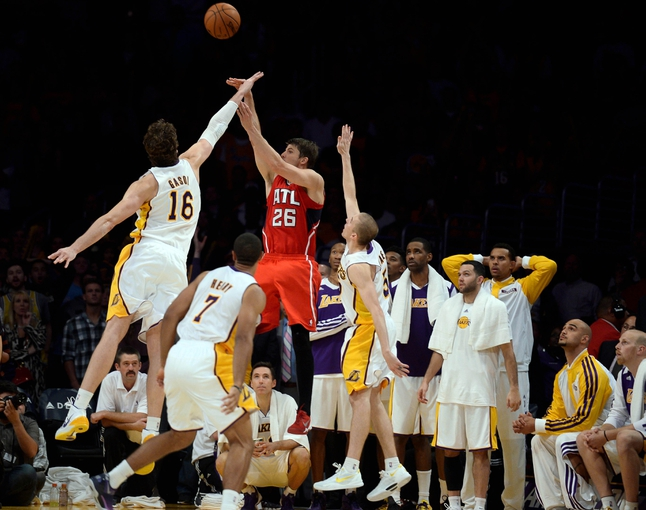 Nov 3, 2013; Los Angeles, CA, USA; Los Angeles Lakers power forward Pau Gasol (16) blocks a last second shot by Atlanta Hawks small forward Kyle Korver (26) in the closing second of the game at Staples Center. The Lakers hung on for a 105-103 win. Mandatory Credit: Robert Hanashiro-USA TODAY Sports
