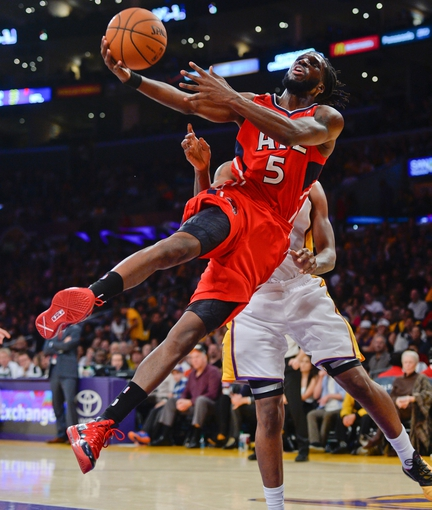 Nov 3, 2013; Los Angeles, CA, USA; Atlanta Hawks small forward DeMarre Carroll (5) goes sideways after getting fouled by Los Angeles Lakers small forward Shawne Williams (3) during second quarter action at Staples Center. Mandatory Credit: Robert Hanashiro-USA TODAY Sports