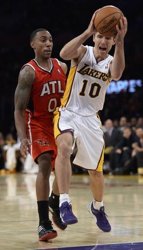 Nov 3, 2013; Los Angeles, CA, USA; Los Angeles Lakers point guard Steve Nash (10) and Atlanta Hawks point guard Jeff Teague (0) during the second half at Staples Center. Mandatory Credit: Robert Hanashiro-USA TODAY Sports