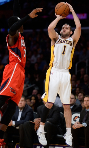 Nov 3, 2013; Los Angeles, CA, USA; Los Angeles Lakers point guard Jordan Farmar (1) shoots a jumper over Atlanta Hawks shooting guard Jared Cunningham (7) during the second half at Staples Center. Mandatory Credit: Robert Hanashiro-USA TODAY Sports