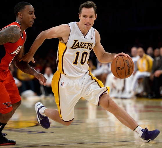 Nov 3, 2013; Los Angeles, CA, USA; Los Angeles Lakers point guard Steve Nash (10) drives around Atlanta Hawks point guard Jeff Teague (0) during the second half at Staples Center. Mandatory Credit: Robert Hanashiro-USA TODAY Sports