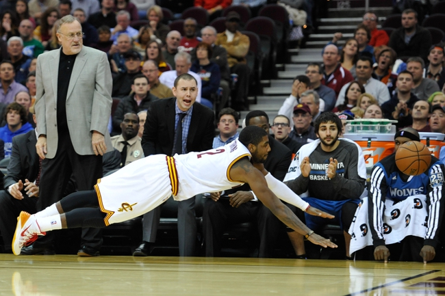 Nov 4, 2013; Cleveland, OH, USA; Minnesota Timberwolves head coach Rick Adelman (left) watches as Cleveland Cavaliers point guard Kyrie Irving (2) dives for a loose ball in the fourth quarter at Quicken Loans Arena. Mandatory Credit: David Richard-USA TODAY Sports