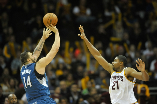 Nov 4, 2013; Cleveland, OH, USA; Minnesota Timberwolves center Nikola Pekovic (14) shoots over Cleveland Cavaliers center Andrew Bynum (21) in the fourth quarter at Quicken Loans Arena. Mandatory Credit: David Richard-USA TODAY Sports