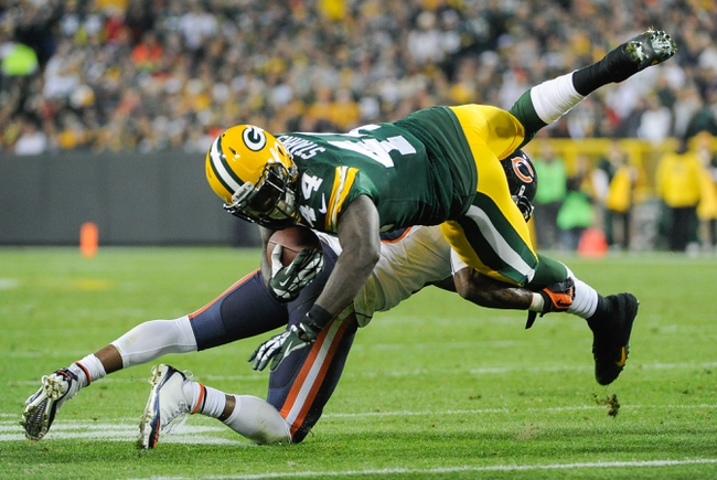Nov 4, 2013; Green Bay, WI, USA;   Green Bay Packers running back James Starks (44) jumps over Chicago Bears cornerback Tim Jennings (26) after a run in the 3rd quarter at Lambeau Field. Mandatory Credit: Benny Sieu-USA TODAY Sports