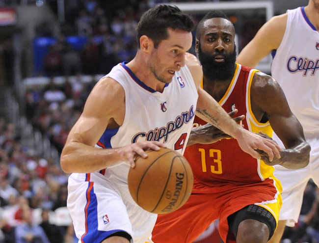 November 4, 2013; Los Angeles, CA, USA; Los Angeles Clippers shooting guard J.J. Redick (4) moves the ball against the defense of Houston Rockets shooting guard James Harden (13) during the second half at Staples Center. Mandatory Credit: Gary A. Vasquez-USA TODAY Sports