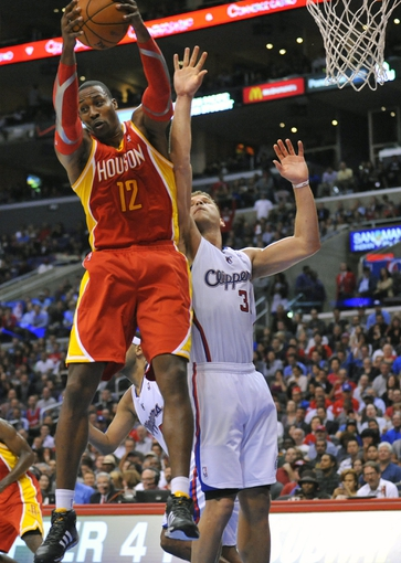 November 4, 2013; Los Angeles, CA, USA; Houston Rockets center Dwight Howard (12) grabs a rebound against the defense of Los Angeles Clippers power forward Blake Griffin (32) during the second half at Staples Center. Mandatory Credit: Gary A. Vasquez-USA TODAY Sports