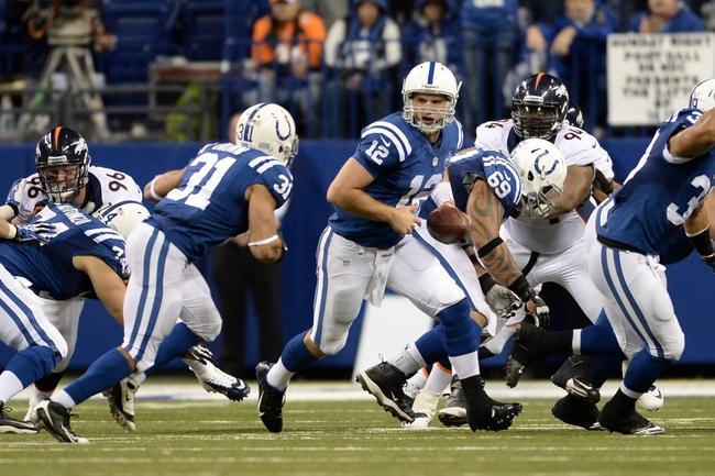 Oct 20, 2013; Indianapolis, IN, USA; Indianapolis Colts quarterback Andrew Luck (12) prepares to hand off to running back Donald Brown (31) in the fourth quarter against the Denver Broncos at Lucas Oil Stadium. The Colts defeated the Broncos 39-33. Mandatory Credit: Ron Chenoy-USA TODAY Sports