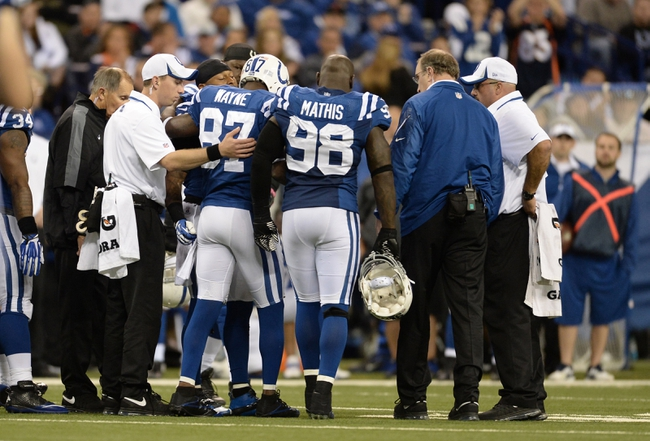 Oct 20, 2013; Indianapolis, IN, USA; Indianapolis Colts wide receiver Reggie Wayne (87) leaves the field after an injury with teammate outside linebacker Robert Mathis (98) during the game against the Denver Broncos at Lucas Oil Stadium. The Colts defeated the Broncos 39-33. Mandatory Credit: Ron Chenoy-USA TODAY Sports