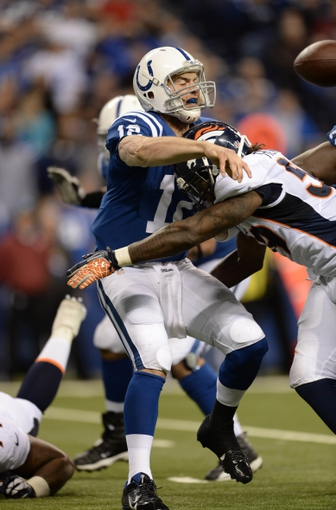 Oct 20, 2013; Indianapolis, IN, USA; Denver Broncos outside linebacker Danny Trevathan (59) hits Indianapolis Colts quarterback Andrew Luck (12) in the fourth quarter at Lucas Oil Stadium. The Colts defeated the Broncos 39-33. Mandatory Credit: Ron Chenoy-USA TODAY Sports