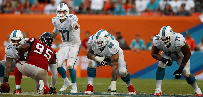 Sep 22, 2013; Miami Gardens, FL, USA;  Miami Dolphins tackle Jonathan Martin (71), guard Richie Incognito (68), and center Mike Pouncey (51) prepare to block for quarterback Ryan Tannehill (17)  as Atlanta Falcons defensive tackle Jonathan Babineaux (95) looks on in the second half at Sun Life Stadium. Miami won 27-23. Mandatory Credit: Robert Mayer-USA TODAY Sports