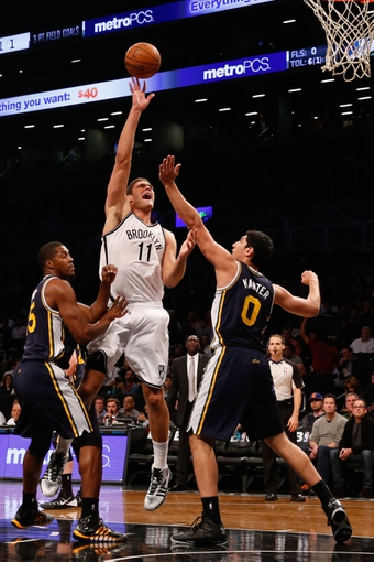 Nov 5, 2013; Brooklyn, NY, USA;  Brooklyn Nets center Brook Lopez (11) shoots over Utah Jazz center Enes Kanter (0) during the first quarter at Barclays Center. Mandatory Credit: Anthony Gruppuso-USA TODAY Sports