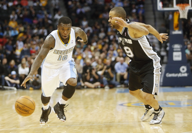 Nov 5, 2013; Denver, CO, USA; Denver Nuggets guard Nate Robinson (10) drives to the basket against San Antonio Spurs guard Tony Parker (9) during the first half at Pepsi Center. Mandatory Credit: Chris Humphreys-USA TODAY Sports