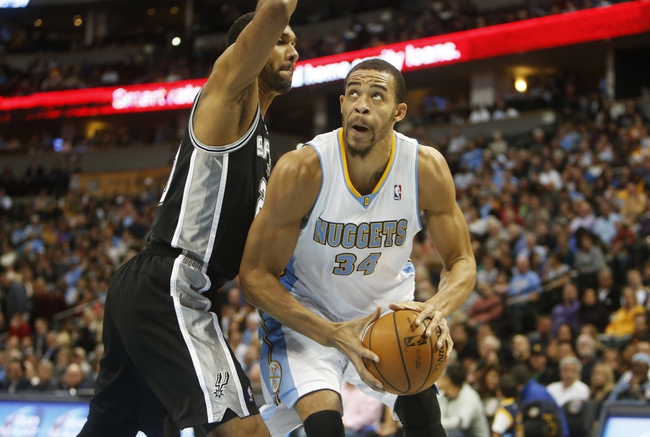Nov 5, 2013; Denver, CO, USA; Denver Nuggets center JaVale McGee (34) drives to the basket against San Antonio Spurs forward Tim Duncan (21) during the first half at Pepsi Center. Mandatory Credit: Chris Humphreys-USA TODAY Sports