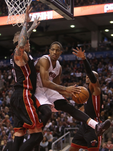 Nov 5, 2013; Toronto, Ontario, CAN; Toronto Raptors guard DeMar DeRozan (10) looks to make a pass under the basket against the Miami Heat at Air Canada Centre. The Heat beat the Raptors 104-95. Mandatory Credit: Tom Szczerbowski-USA TODAY Sports