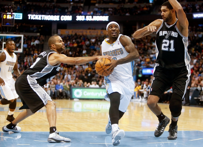 Nov 5, 2013; Denver, CO, USA; Denver Nuggets guard Ty Lawson (3) drives to the basket between San Antonio Spurs guard Tony Parker (9) and forward Tim Duncan (21) during the first half at Pepsi Center. Mandatory Credit: Chris Humphreys-USA TODAY Sports