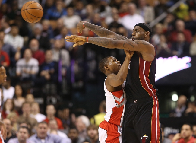 Nov 5, 2013; Toronto, Ontario, CAN; Miami Heat forward LeBron James (6) passes under pressure from Toronto Raptors point guard Kyle Lowry (7) at Air Canada Centre. The Heat beat the Raptors 104-95. Mandatory Credit: Tom Szczerbowski-USA TODAY Sports