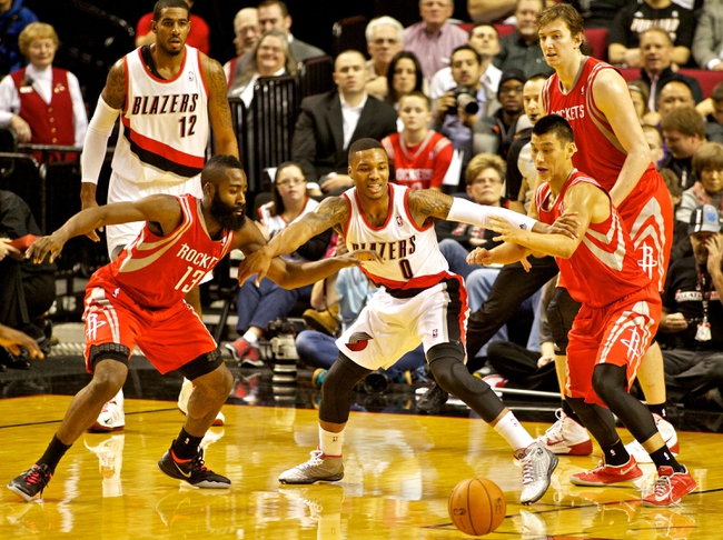 Nov 5, 2013; Portland, OR, USA; Portland Trail Blazers point guard Damian Lillard (0), Houston Rockets shooting guard James Harden (13) and point guard Jeremy Lin (7) fight for a loose ball at the Moda Center. Mandatory Credit: Craig Mitchelldyer-USA TODAY Sports