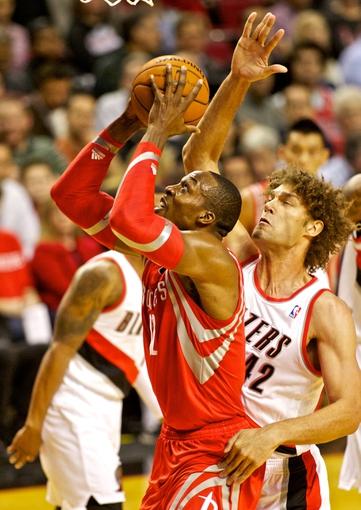 Nov 5, 2013; Portland, OR, USA; Houston Rockets center Dwight Howard (12) shoots over Portland Trail Blazers center Robin Lopez (42) at the Moda Center. Mandatory Credit: Craig Mitchelldyer-USA TODAY Sports