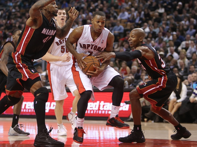 Nov 5, 2013; Toronto, Ontario, CAN; Toronto Raptors point guard Kyle Lowry (7) goes to the basket against Miami Heat guard Ray Allen (34) and forward Udonis Haslem (40) at Air Canada Centre. The Heat beat the Raptors 104-95. Mandatory Credit: Tom Szczerbowski-USA TODAY Sports