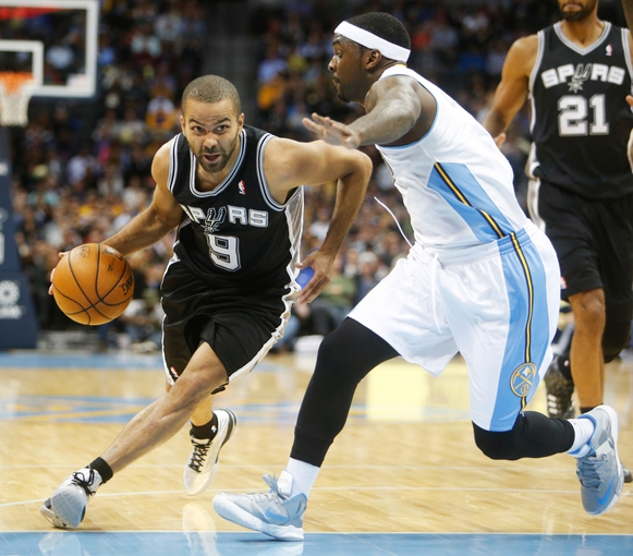Nov 5, 2013; Denver, CO, USA; San Antonio Spurs guard Tony Parker (9) drives to the basket against Denver Nuggets guard Ty Lawson (3) during the second half at Pepsi Center. The Spurs won 102-94. Mandatory Credit: Chris Humphreys-USA TODAY Sports