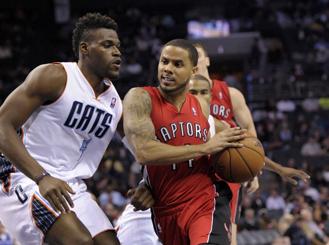 Nov 6, 2013; Charlotte, NC, USA; Toronto Raptors guard D.J. Augustin (14) drives to the basket as he is defended by Charlotte Bobcats forward Jeff Adrien (4) during the game at Time Warner Cable Arena. Mandatory Credit: Sam Sharpe-USA TODAY Sports