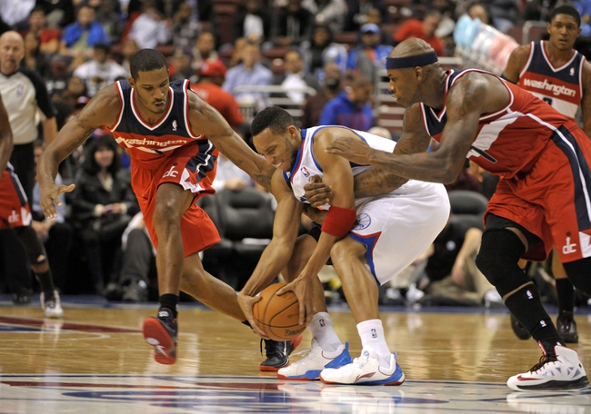 Nov 6, 2013; Philadelphia, PA, USA; Philadelphia 76ers small forward Evan Turner (12) battles with Washington Wizards small forward Trevor Ariza (1) and power forward Al Harrington (7) during the first half at Wells Fargo Center. Mandatory Credit: Eric Hartline-USA TODAY Sports
