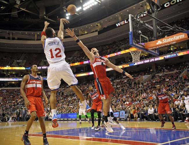 Nov 6, 2013; Philadelphia, PA, USA; Philadelphia 76ers small forward Evan Turner (12) shots over Washington Wizards center Marcin Gortat (4) during the second half at Wells Fargo Center. The Wizards defeated the 76ers, 116-102. Mandatory Credit: Eric Hartline-USA TODAY Sports