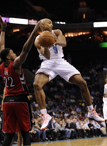 Nov 6, 2013; Charlotte, NC, USA; Charlotte Bobcats guard Gerald Henderson (9) passes the ball as he is defended by Toronto Raptors forward Rudy Gay (22) during the game at Time Warner Cable Arena. Bobcats win 92-90. Mandatory Credit: Sam Sharpe-USA TODAY Sports