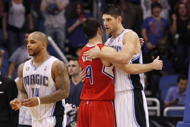 Nov 6, 2013; Orlando, FL, USA; Los Angeles Clippers shooting guard J.J. Redick (4) and Orlando Magic center Nikola Vucevic (9) hug after the game at Amway Center. Orlando Magic defeated the Los Angeles Clippers 98-90. Mandatory Credit: Kim Klement-USA TODAY Sports