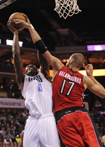 Nov 6, 2013; Charlotte, NC, USA; Charlotte Bobcats forward center Bismack Biyombo (0) drives to the basket as he is defended by Toronto Raptors center Jonas Valanciunas (17) during the game at Time Warner Cable Arena. Bobcats win 92-90. Mandatory Credit: Sam Sharpe-USA TODAY Sports