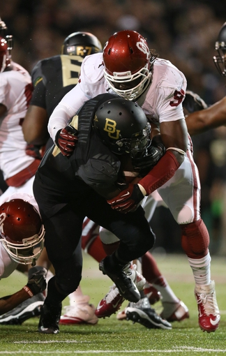 Nov 7, 2013; Waco, TX, USA; Oklahoma Sooners defensive end Charles Tapper (91) tackles Baylor Bears running back Glasco Martin (8) in the first quarter at Floyd Casey Stadium. Mandatory Credit: Matthew Emmons-USA TODAY Sports