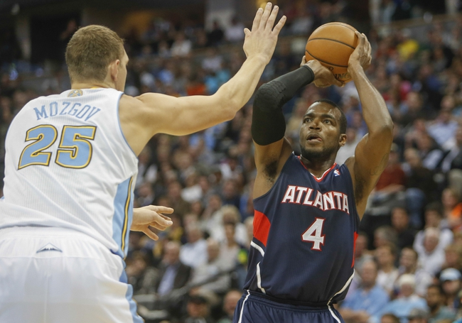 Nov 7, 2013; Denver, CO, USA;  Atlanta Hawks forward Paul Millsap (4) shoots the ball over Denver Nuggets center Timofey Mozgov (25) during the second half at Pepsi Center. The Nuggets won 109-107. Mandatory Credit: Chris Humphreys-USA TODAY Sports