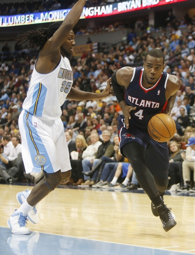 Nov 7, 2013; Denver, CO, USA;  Atlanta Hawks forward Paul Millsap (4) drives to the basket against Denver Nuggets forward Kenneth Faried (35) during the second half at Pepsi Center. The Nuggets won 109-107. Mandatory Credit: Chris Humphreys-USA TODAY Sports