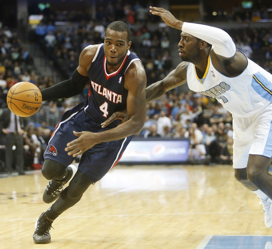 Nov 7, 2013; Denver, CO, USA;  Atlanta Hawks forward Paul Millsap (4) drives to the basket against Denver Nuggets forward J.J. Hickson (7) during the second half at Pepsi Center. The Nuggets won 109-107. Mandatory Credit: Chris Humphreys-USA TODAY Sports