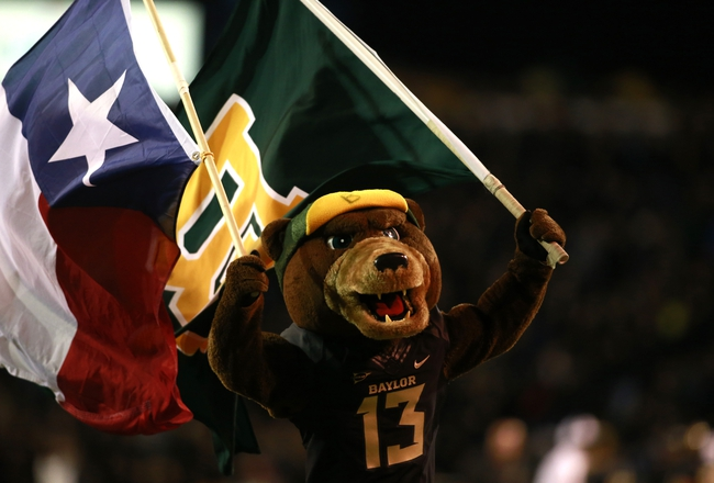 Nov 7, 2013; Waco, TX, USA;  Baylor Bears mascot Bruiser runs on the field with a Texas state flag and a Baylor flag after a touchdown in the game against the Oklahoma Sooners at Floyd Casey Stadium. Baylor beat Oklahoma 41-12.  Mandatory Credit: Tim Heitman-USA TODAY Sports